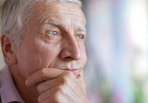 Mann grübelt, ob Stress die Ursache seiner Inkontinenz ist.