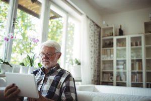 Mann am Tablet informiert sich über Urinverlust durch die Prostata.